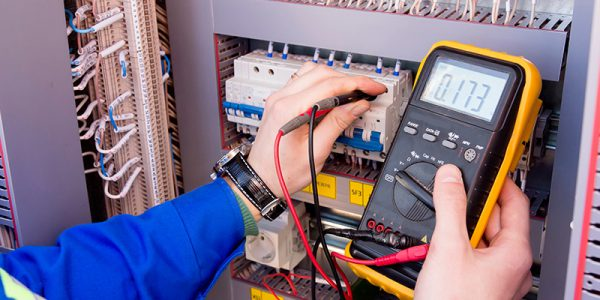 Canva---multimeter-is-in-hands-of-engineer-in-electrical-cabinet.-Adjustment-of-automated-control-system-for-industrial-equipment-control-cabinets.-electrician-measures-voltage-by-tester.